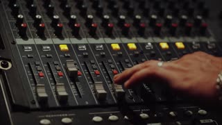 Recording studios audio console and a hand pulling up the knobs