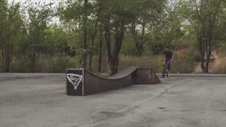 Ryder by bicycle jumps through an obstacle and lands on a plain surface.