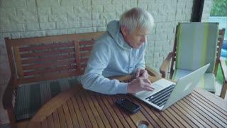 Senior man online shopping with laptop computer entering credit card information