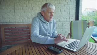 Senior man online shopping with laptop computer entering credit card information