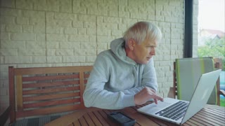 Senior man surfing on internet outside the house sitting on the porch