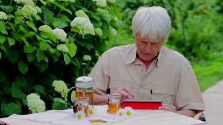 Senior man using digital tablet in summer garden table with tea