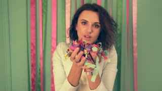 Slow motion shot of brunette woman at the party inflates confetti on all room