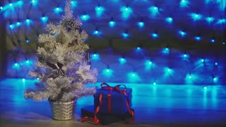 Small silver Xmas tree with gifts. Christmas and New Year celebration.