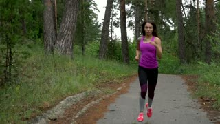 sport workout outdoors. Sport woman running through the woods. slow motion.