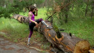 Sporty girl in the forest. Perform stretching. Look at the camera and smiling 4K
