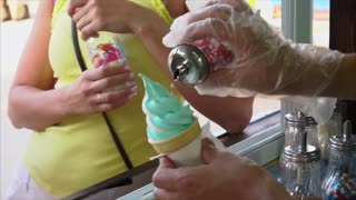 Street vendor sprinkles ice cream waffle cone by sugar red hearts