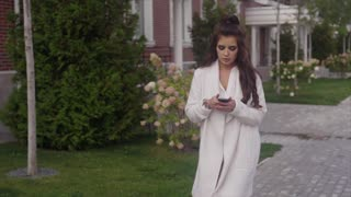 Successful young business woman walking down the street using her smartphone