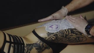 Tattoo artist preparing skin of his client to the process of making tattoo