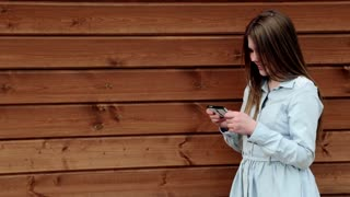 Teenage girl holding her smartphone in cute pose wooden background copy space