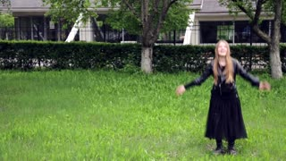 Teenage girl jumping and spinning crazy emotions in park
