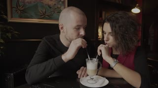 The man with tube into a joke smears on the nose of his girlfriend crema coffee.