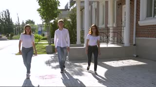 Three girls and boy dressed in similar jeans and shirts dancing in the street