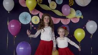 Two baby girls sisters waving and celebrating on birthday party