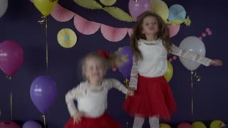 Two pretty baby girls sisters dancing and celebrating on birthday party