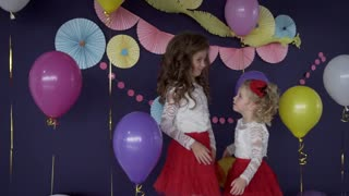 Two pretty baby girls sisters hugging and celebrating on birthday party