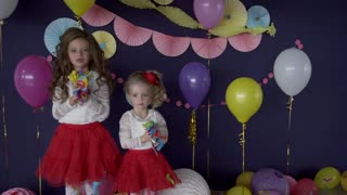 Two pretty baby girls sisters throwing bright confetti and celebrating birthday