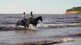 Two women ride on horse at river beach in water sunset light