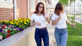 Two young hipster girl friends dancing outdoor slow motion