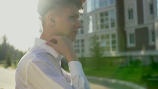 Video portrait of young teenage boy outdoor on the city street slow motion