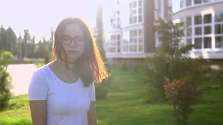 Video portrait teenage girl wearing glasses walking in the park shaking hair