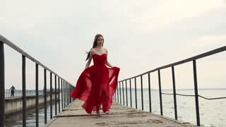 a beautiful woman with curly hair runs quickly down the pier along the sea, the lady is in a hurry and supports the hem of the red dress so as not to stumble