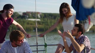 A company of young happy friends sail on a yacht on a summer day, friends share interesting stories about their life style with each other, men and women relax in the sun