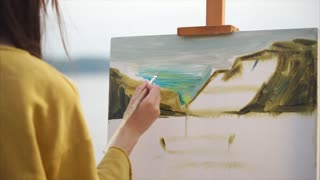A creative woman paints a painting with oil paints on canvas, which stands on the easel, the young artist went to the open-air to paint the still life of the sea and mountains