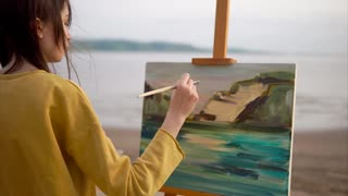 A cute and creative teenager draws a still life from nature, the canvas stands on the easel. An irascible girl draws the sea and mountains in the Impressionist style, she uses a palette with oil