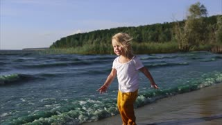 A cute and funny child runs on the water, the boy is on the nature near a lake or river, strong wind and waves prevent him from going confidently