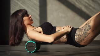 A cute and young athlete uses a foam roller for exercise in a fitness club, a woman with a tattoo lay on a roller and massages her back to warm her up
