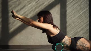 A cute and young athlete uses a foam roller for exercise in the fitness club, a woman with a tattoo on her body pumps the back muscles on sports equipment