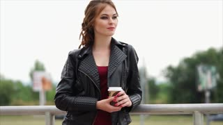 A cute and young woman with a bright make-up who smiles and looks into the distance holding a cup of coffee in her hand, the lady is holding a glass with a hot drink