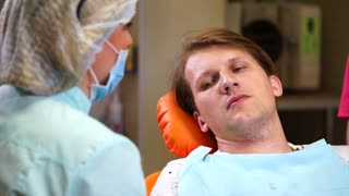 A female dentist talks with a patient in a private clinic, the doctor tells what he will do with the mouth of a man. The dentist wants to clean caries from the teeth
