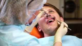 A female doctor who examines the oral cavity of a patient with a dental mirror checks teeth for caries and other damage caused by poor hygiene.
