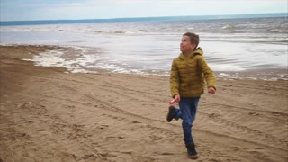 A joyful little boy runs quickly over dry sand near the sea with a kite in his hand, the child is happy to have a day off on the beach in cold weather