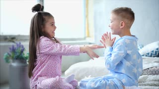 A kind boy and a pretty girl dressed in cute pajamas play a game on their hands. Children who sit on the bed in the bedroom are happy and fooling around, slapping their hands on their hands