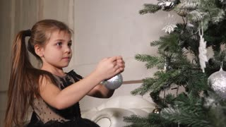 a little girl in a smart dress decorates the Christmas tree with shiny balls, the child hangs bright toys on the New Year tree to create a festive atmosphere before the upcoming family holiday
