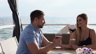 A man and a pretty woman who drinks wine choose to wait for their dinner at the restaurant, a couple in love sits on the veranda near the sea or river, newlyweds clink glasses