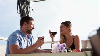 A man and a pretty woman who drinks wine from glasses spend time in a restaurant, a couple in love sits on a veranda near a sea or a river, newlyweds clink glasses and talk to each other