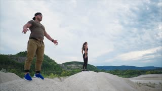 A man and a woman enjoy nature after training, the athlete makes breathing exercises on top of a sand hill, the person raises his hands up and takes a deep breath