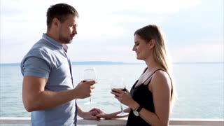 A man and a woman who flirt with each other clink glasses with wine, the couple celebrate the anniversary of marriage in a restaurant with an open terrace