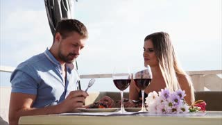 A man and a woman who looks like a newly-married couple, communicate with each other in a restaurant by the water, the couple eat an appetizing apperictive and drink wine from glasses