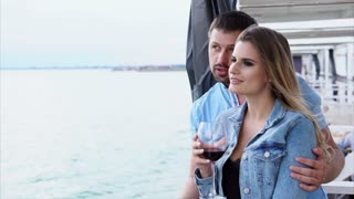 A man and his beautiful woman who holds a glass of wine in their hand ride the ship during the day, lovers embrace and happily spend time in the summer season