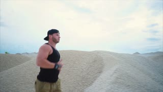 A man who goes in for sports runs through the sand park in order to perform cardio exercises, the athlete actively trains before physical exercises