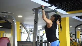 A middle-aged woman pulling herself up on a simulator in a fitness club. The athlete wants to bring her body in a good physical shape before the beach season.