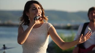 A modern and young singer performs a song in the daytime, a woman sings into an open-air microphone, an energetic melody makes her dance