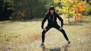 A nice and young woman in a sports suit is engaged in warming up the muscles in nature, the lady is going to start running during a summer day in the park