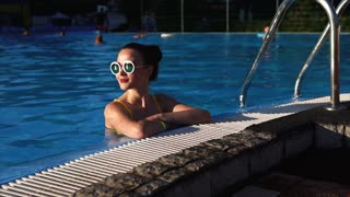 A nice and young woman in stylish glasses and a bathing suit is in the pool, the lady enjoys cool water on a hot sunny day of her day off