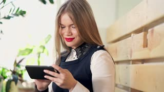 A nice and young woman looks at photos and puts the likes of social networks on a mobile phone. A lady with red lipstick smiles, watching the news on the smartphone